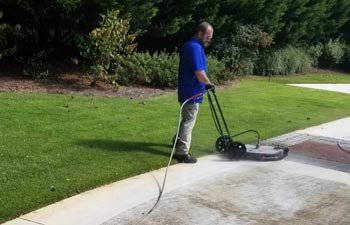 a man cleaning the paver in the yard