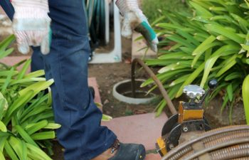 Sewer cleaning. A plumber uses a sewer snake to clean blockage in a sewer line